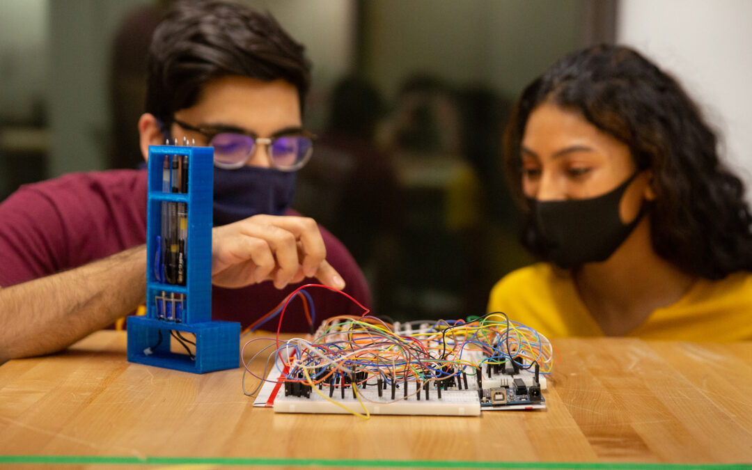 A male and female student in a work session looking at circuitry